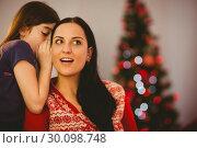 Купить «Daughter telling her mother a christmas secret», фото № 30098748, снято 24 июля 2014 г. (c) Wavebreak Media / Фотобанк Лори