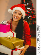 Купить «Festive brunette smiling at camera», фото № 30098908, снято 24 июля 2014 г. (c) Wavebreak Media / Фотобанк Лори
