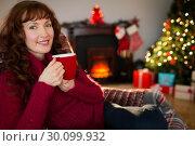 Купить «Pretty redhead enjoying hot drink at christmas», фото № 30099932, снято 3 октября 2014 г. (c) Wavebreak Media / Фотобанк Лори