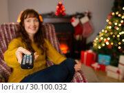 Купить «Happy redhead changing channel at christmas», фото № 30100032, снято 3 октября 2014 г. (c) Wavebreak Media / Фотобанк Лори