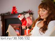 Купить «Relaxed redhead reading on the couch at christmas», фото № 30100132, снято 3 октября 2014 г. (c) Wavebreak Media / Фотобанк Лори