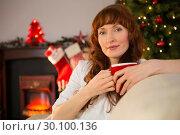 Купить «Pretty redhead holding a mug of hot chocolate at christmas», фото № 30100136, снято 3 октября 2014 г. (c) Wavebreak Media / Фотобанк Лори