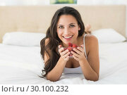 Купить «Happy brunette with bowl of strawberries», фото № 30100232, снято 2 октября 2014 г. (c) Wavebreak Media / Фотобанк Лори