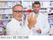 Купить «Pharmacist holding a box of pills while reading the label», фото № 30100548, снято 13 сентября 2014 г. (c) Wavebreak Media / Фотобанк Лори