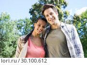 Happy couple smiling at camera in park. Стоковое фото, агентство Wavebreak Media / Фотобанк Лори