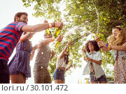 Купить «Happy hipsters spraying beer bottles», фото № 30101472, снято 19 ноября 2014 г. (c) Wavebreak Media / Фотобанк Лори