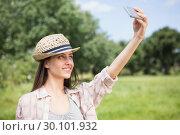 Купить «Pretty brunette taking a selfie in park», фото № 30101932, снято 11 ноября 2014 г. (c) Wavebreak Media / Фотобанк Лори