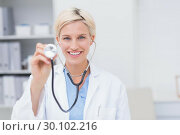 Happy female doctor holding stethoscope. Стоковое фото, агентство Wavebreak Media / Фотобанк Лори