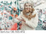 Купить «Smiling woman is buying Christmas wreath in the market», фото № 30103472, снято 21 декабря 2017 г. (c) Яков Филимонов / Фотобанк Лори