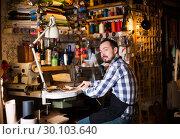 Купить «Male worker stitching new belt», фото № 30103640, снято 21 августа 2019 г. (c) Яков Филимонов / Фотобанк Лори