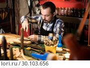 Купить «Young man worker processing leather», фото № 30103656, снято 26 марта 2019 г. (c) Яков Филимонов / Фотобанк Лори