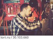 Купить «Worker processing leather for belt», фото № 30103660, снято 26 марта 2019 г. (c) Яков Филимонов / Фотобанк Лори