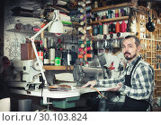 Купить «male worker sewing stitches on belt in leather workshop», фото № 30103824, снято 21 июля 2019 г. (c) Яков Филимонов / Фотобанк Лори