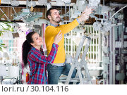 Купить «Young man and woman are choosing stylish and modern chandelier lamp.», фото № 30104116, снято 16 февраля 2017 г. (c) Яков Филимонов / Фотобанк Лори