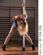 Купить «Young woman in denim shorts practicing pole dancing», фото № 30104396, снято 21 февраля 2019 г. (c) Яков Филимонов / Фотобанк Лори