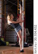 Купить «Young woman in denim shorts practicing pole dancing», фото № 30104432, снято 22 апреля 2019 г. (c) Яков Филимонов / Фотобанк Лори