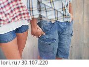 Купить «Composite image of couple in check shirts and denim holding hands», фото № 30107220, снято 19 января 2015 г. (c) Wavebreak Media / Фотобанк Лори