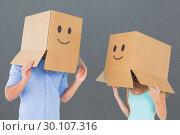 Купить «Composite image of couple wearing emoticon face boxes on their heads», фото № 30107316, снято 19 января 2015 г. (c) Wavebreak Media / Фотобанк Лори