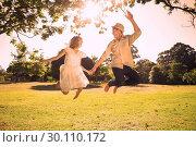 Купить «Cute couple jumping in the park together holding hands», фото № 30110172, снято 31 января 2014 г. (c) Wavebreak Media / Фотобанк Лори