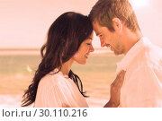 Купить «Romantic couple relaxing and embracing on the beach », фото № 30110216, снято 3 апреля 2013 г. (c) Wavebreak Media / Фотобанк Лори