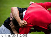 Купить «Rugby players doing a scrum», фото № 30112008, снято 9 сентября 2015 г. (c) Wavebreak Media / Фотобанк Лори