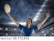 Composite image of happy rugby player in blue jersey holding ball with arms raised. Стоковое фото, агентство Wavebreak Media / Фотобанк Лори