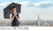 Купить «Composite image of pretty redhead businesswoman holding umbrella», фото № 30114240, снято 5 февраля 2016 г. (c) Wavebreak Media / Фотобанк Лори