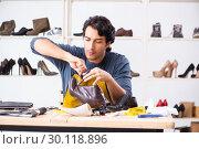 Купить «Young man repairing shoes in workshop», фото № 30118896, снято 22 октября 2018 г. (c) Elnur / Фотобанк Лори