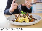 Купить «Man taking photograph of meal», фото № 30119756, снято 12 апреля 2016 г. (c) Wavebreak Media / Фотобанк Лори