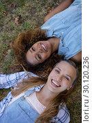 Купить «Female friends lying together on grass in park», фото № 30120236, снято 20 июля 2016 г. (c) Wavebreak Media / Фотобанк Лори