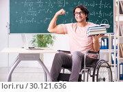 Купить «Young handsome man in wheelchair in front of chalkboard», фото № 30121636, снято 23 ноября 2018 г. (c) Elnur / Фотобанк Лори