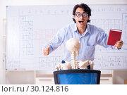 Купить «Young male chemist teacher and student skeleton», фото № 30124816, снято 19 октября 2018 г. (c) Elnur / Фотобанк Лори
