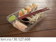 Купить «Uramaki and nigiri sushi served with chopsticks and soy sauce in plastic box», фото № 30127608, снято 8 декабря 2016 г. (c) Wavebreak Media / Фотобанк Лори