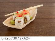 Купить «Four uramaki sushi served with chopsticks in wooden boat plate», фото № 30127624, снято 8 декабря 2016 г. (c) Wavebreak Media / Фотобанк Лори
