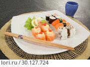 Купить «Assorted sushi set served with chopsticks and glass on sushi mat», фото № 30127724, снято 8 декабря 2016 г. (c) Wavebreak Media / Фотобанк Лори