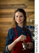 Купить «Waitress using a tamper to press ground coffee into a portafilter», фото № 30128672, снято 12 октября 2016 г. (c) Wavebreak Media / Фотобанк Лори