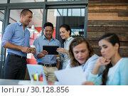 Купить «Businesspeople having discussion over digital tablet», фото № 30128856, снято 16 октября 2016 г. (c) Wavebreak Media / Фотобанк Лори