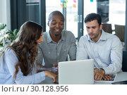Купить «Team of graphic designers discussing over laptop», фото № 30128956, снято 16 октября 2016 г. (c) Wavebreak Media / Фотобанк Лори
