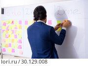 Купить «Young handsome employee in front of whiteboard with to-do list», фото № 30129008, снято 16 октября 2018 г. (c) Elnur / Фотобанк Лори