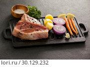 Купить «Sirloin chop and ingredients on black grill», фото № 30129232, снято 20 сентября 2016 г. (c) Wavebreak Media / Фотобанк Лори
