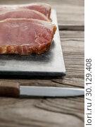 Купить «Sirloin chop on black slate plate with knife», фото № 30129408, снято 20 сентября 2016 г. (c) Wavebreak Media / Фотобанк Лори