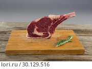 Купить «Rib chop steak and rosemary herb on wooden board against wooden background», фото № 30129516, снято 20 сентября 2016 г. (c) Wavebreak Media / Фотобанк Лори