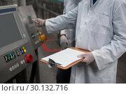 Купить «Two factory engineers operating machine in factory», фото № 30132716, снято 20 октября 2016 г. (c) Wavebreak Media / Фотобанк Лори