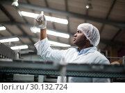 Купить «Factory engineers checking a sample of drink», фото № 30132724, снято 20 октября 2016 г. (c) Wavebreak Media / Фотобанк Лори