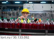 Купить «Male factory worker monitoring cold drink bottles», фото № 30133092, снято 20 октября 2016 г. (c) Wavebreak Media / Фотобанк Лори