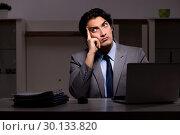 Купить «Young handsome employee and too much work in the office», фото № 30133820, снято 15 ноября 2018 г. (c) Elnur / Фотобанк Лори