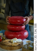 Купить «Mid section of salesman holding stacked gouda cheese», фото № 30134188, снято 4 октября 2016 г. (c) Wavebreak Media / Фотобанк Лори