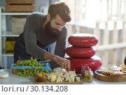 Купить «Salesman arranging cheese at counter», фото № 30134208, снято 4 октября 2016 г. (c) Wavebreak Media / Фотобанк Лори