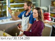 Купить «Shop assistants looking at olive oil and pickle bottles », фото № 30134280, снято 4 октября 2016 г. (c) Wavebreak Media / Фотобанк Лори