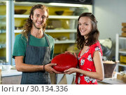 Купить «Portrait of salesman and costumer holding gouda cheese at counter», фото № 30134336, снято 4 октября 2016 г. (c) Wavebreak Media / Фотобанк Лори